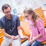 Zahnarzt Dr. Mark Stephan Lindner berät eine junge Patientin