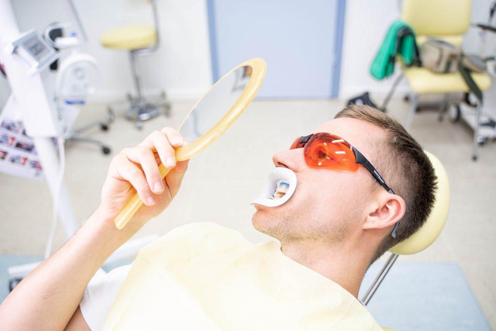 Patient schaut sich das Zwischenergebnis der Zahnaufhellung an